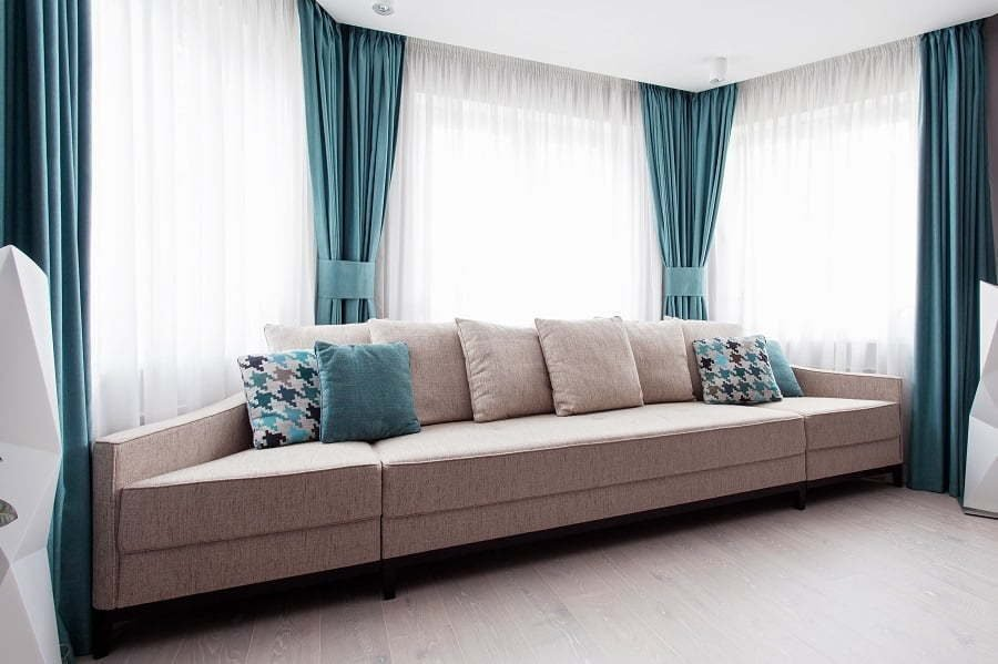 large-modern-couch-in-the-room-near-a-big-window-light-and-turquoise-tones